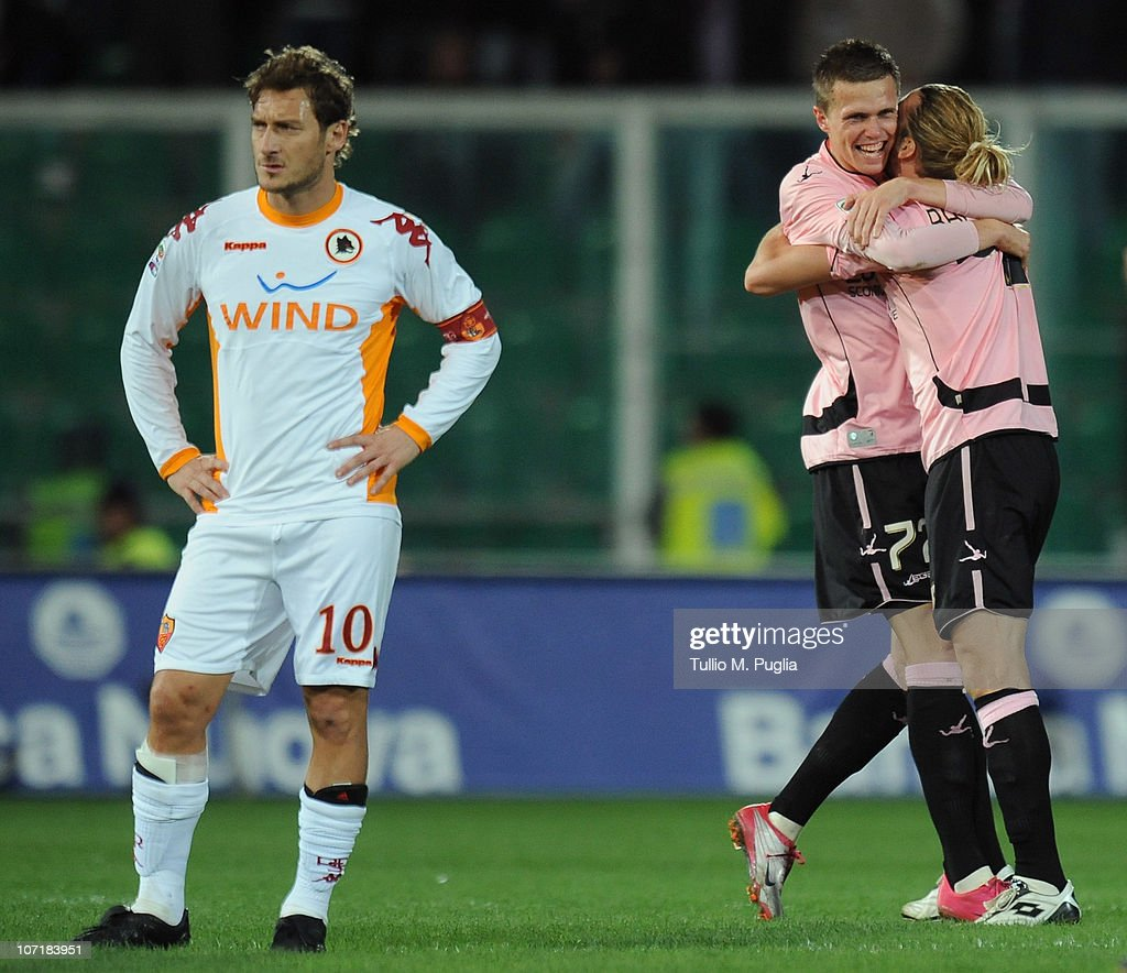 Pajtim Ilicic (C) of Palermo celebrates after scoring the 2nd goal with his team mate Federico Balzaretti (R) as Francesco Totti (L) of Roma looks dejected, during the Serie A match between Palermo and Roma at Stadio Renzo Barbera on November 28, 2010 in Palermo, Italy.