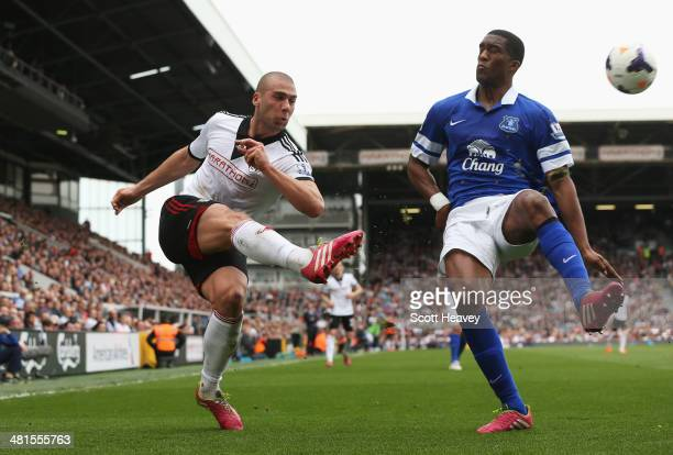 Pajtim Kasami of Fulham crosses as he is closed down by Sylvain Distin of Everton during the Barclays Premier League match between Fulham and Everton...