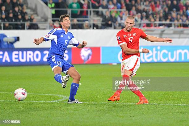 Pajtim Kasami of Switzerland scores the fifth goal as Matteo Coppini of San Marino defends during the UEFA EURO 2016 qualifier between Switzerland...