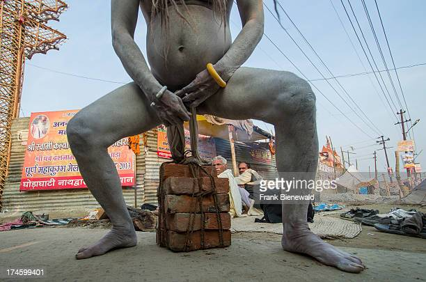 Paket of bricks getting lifted by the penis of a Shiva sadhu from Avahan Akhara holy man at the Sangam the confluence of the rivers Ganges Yamuna and...