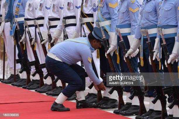 Pakistan Air Force officer adjusts the shoes of his colleague prior to a farewell ceremony of Pakistan President Asif Ali Zardari at the Presidential...