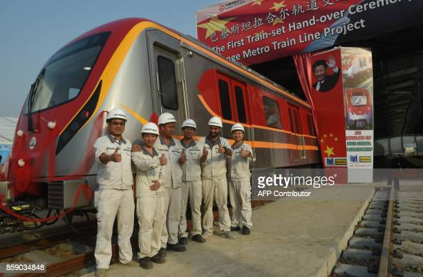 Pakistan and Chinese staff of Lahore Orange Line MetroTrain pose the thumbs up during the unveiling ceremony of the first set of carriages of Lahore...
