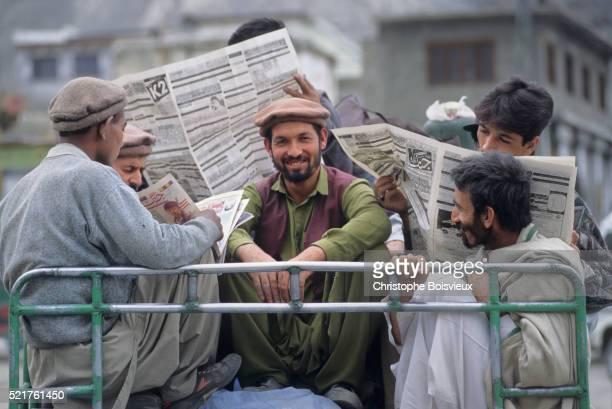 Pakistan, Baltistan, Skardu, Men reading newpapers on top of a bus