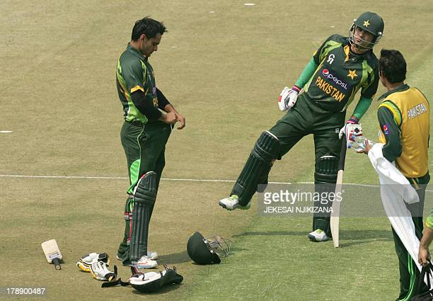 Pakistan batsman Muhammad Hafeez with team mate Ahmed Shehzad tucks in after receiving treatment for a hamstring injury during the final game of the...
