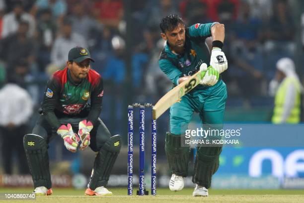 Pakistan batsman Shoaib Malik plays a shot as Bangladesh wicketkeeper Mushfiqur Rahim looks on during the one day international Asia Cup cricket...