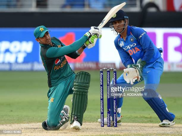 Pakistan batsman Shoaib Malik plays a shot as Indian wicketkeeper Mahendra Singh Dhoni looks on during the one day international Asia Cup cricket...
