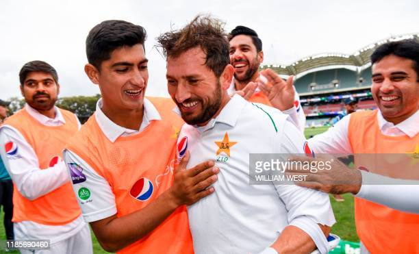 TOPSHOT Pakistan batsman Yasir Shah is congratulated by teammates after scoring his century against Australia on the third day of the second cricket...