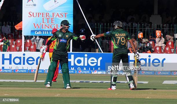 Pakistan batsmans Muhammad Hafeez and Azhar Ali celebrate during the first One Day International match between Pakistan and Zimbabwe at the Gaddafi...