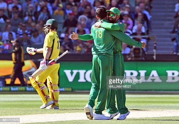 Pakistan bowler Shoaib Malik is congratulated by teammate Mohammad Hafeez after dismissing Australia's batsman Matthew Wade during their oneday...