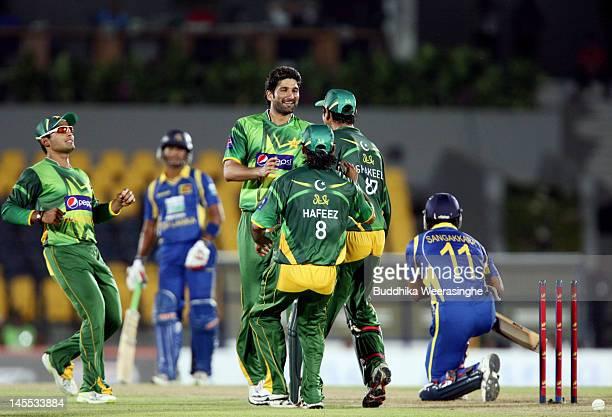 Pakistan bowler Sohail Tanvir celebrates with teammate after taking the wicket of Sri Lankan batsman Kumara Sangakkara during the 1st match of the...
