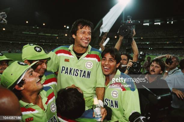 Pakistan captain Imran Khan celebrates with team mates as photographer David Munden looks on after the 1992 Cricket World Cup Final victory against...
