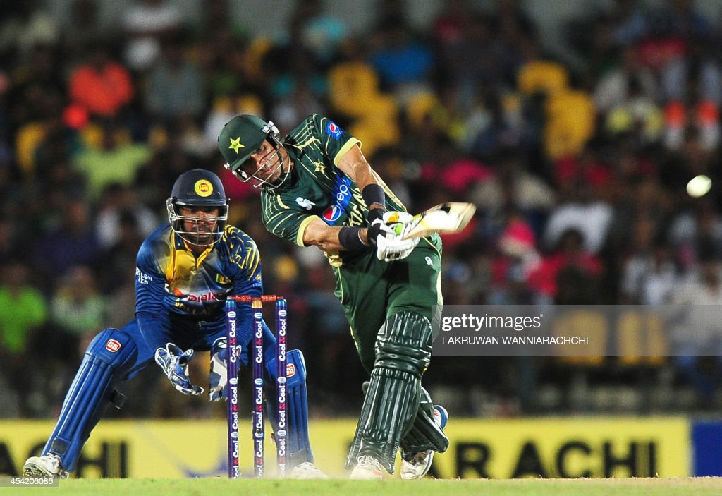 Pakistan captain Misbah-ul Haq (R) is watched by Sri Lankan wicketkeeper Kumar Sangakkara as he plays a shot during the second One Day International (ODI) match between Sri Lanka and Pakistan at the Suriyawewa Mahinda Rajapakse International Cricket Stadium in the southern district of Hambantota on August 26, 2014.