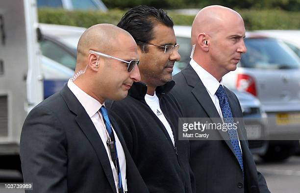 Pakistan coach Waqar Younis is escorted by security into the Holiday Inn and speaks with the waiting media on August 31 2010 in Taunton England The...