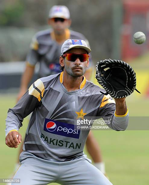 Pakistan cricket captain Mohammad Hafeez catches a ball with a baseball glove during a practice session at the Galle International Stadium in Galle...