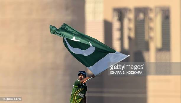 A Pakistan cricket fan waves a flag in support of his national team during the one day international Asia Cup cricket match between Bangladesh and...