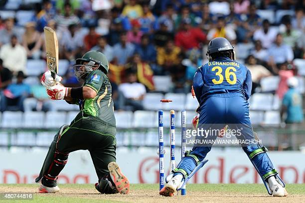 Pakistan cricketer Ahmed Shehzad gets dismissed by Sri Lankan cricketer Sachith Pathirana as wicketkeeper Dinesh Chandimal looks on during the second...