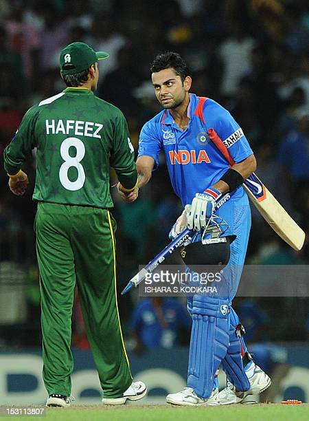 Pakistan cricketer Mohammad Hafeez is congratulated by Indian cricketers Virat Kohli after India's victory on September 30 2012 during the ICC...