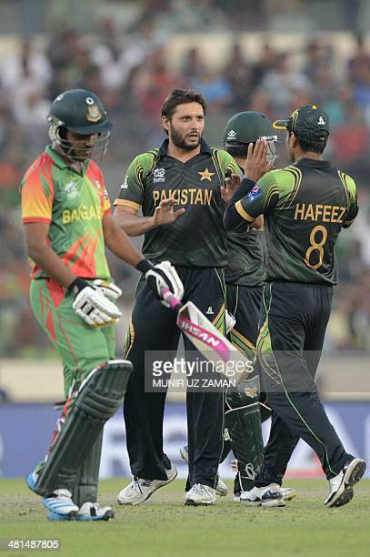 Pakistan cricketer Shahid Afridi celebrates with captain Mohammad Hafeez after the dismissal of Bangladesh cricketer Shamsur Rahman during the ICC...