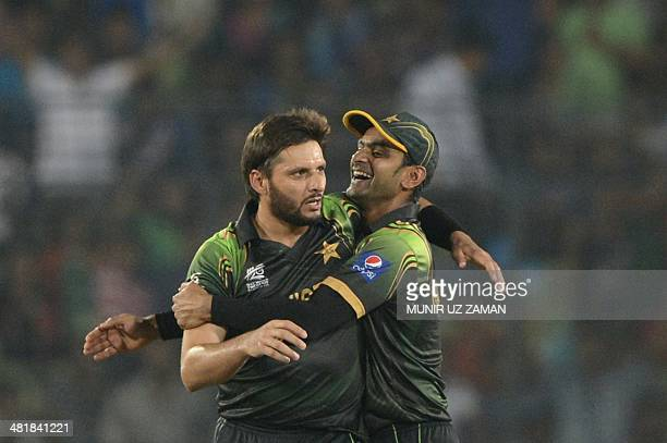 Pakistan cricketer Shahid Afridi celebrates with his captain Mohammad Hafeez after the dismissal of the West Indies cricketer Marlon Samuels during...