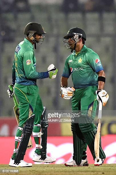 Pakistan cricketer Shoaib Malik talks to his teammate Umar Akmal during the Asia Cup T20 cricket tournament match between Pakistan and Sri Lanka at...