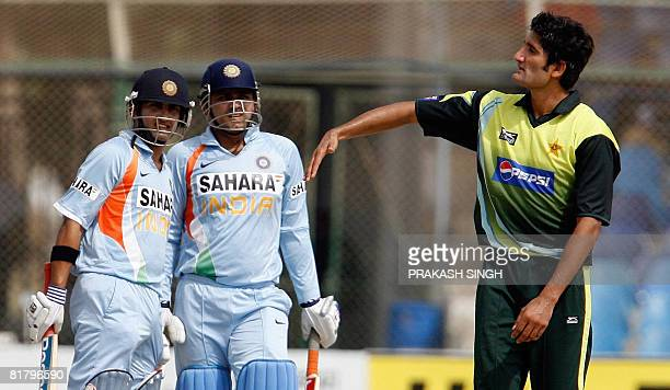 Pakistan cricketer Sohail Tanveer gestures as Indian cricketers Gautam Gambhir and Virender Sehwag watch a six batted by Sehwag during the Super...