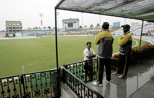 Pakistan cricketers Asim Kamal and Yousuf Yohana take shelter as rain suspends play at the PCA stadium in Mohali 09 March 2005 the second day of the..