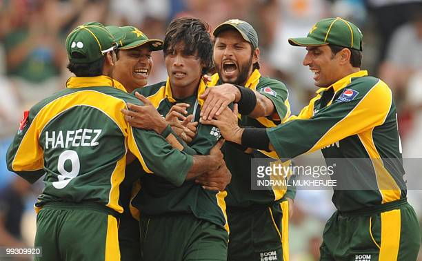 Pakistan cricketers congratulate teammate Mohammad Aamer as they celebrate the wicket of Australian cricketer Shane Watson during the ICC World...