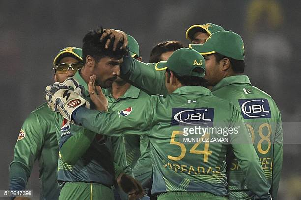 Pakistan cricketers congratulate teammate Mohammad Amir after the dismissal of Indian cricketer Ajinkya Rahane during the match between India and...