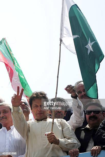 Pakistan cricketerturnedpolitician Imran Khan flashes a victory sign as he heads a protest march from Lahore to Islamabad against the government in...