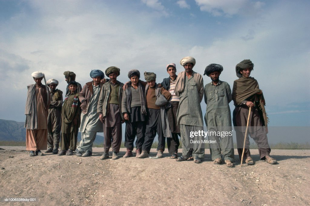 Pakistan, Darra, group portrait of men and teenage boys (13-14) on mountain raod