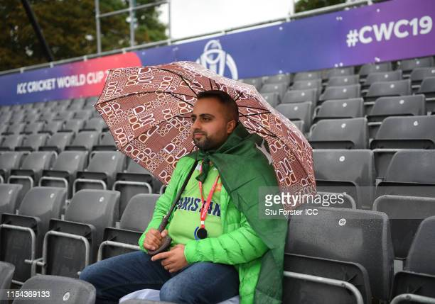 Pakistan fan pictured as rain falls and delays the start of the Group Stage match of the ICC Cricket World Cup 2019 between Pakistan and Sri Lanka at...