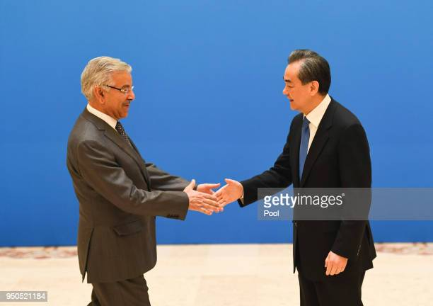 Pakistan Foreign Minister Khawaja Muhammad Asif shakes hands with Chinese State Councilor and Foreign Minister Wang Yi before a meeting of foreign...