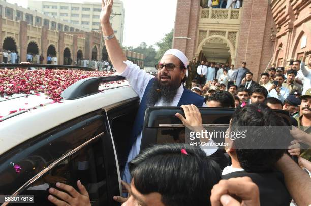 Pakistan head of the JamaatudDawa organisation Hafiz Saeed waves to supporters as he leaves a court in Lahore on October 19 2017 Saeed designated a...