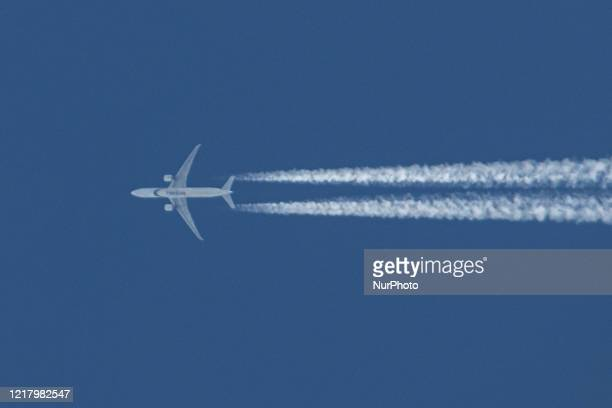 Pakistan International Airlines PIA Boeing 777-300 aircraft as seen flying in the Greek summer blue sky over the city of Thessaloniki in Greece. The...
