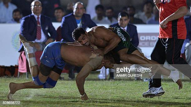 A Pakistan kabaddi player is tackled by an Indian opponent during their final match of the 3rd Asian Kabaddi Circle Style Championship 2016 in Wah...