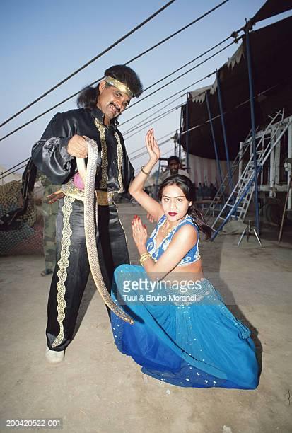 pakistan, lahore, hijra dancing by man holding snake, portrait - hijra pakistan stock pictures, royalty-free photos & images