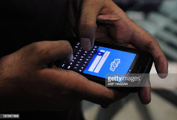 A Pakistan man tries to connect to the Skype network on his mobile in the port city of Karachi on October 3 2013 Pakistan's southern Sindh province...