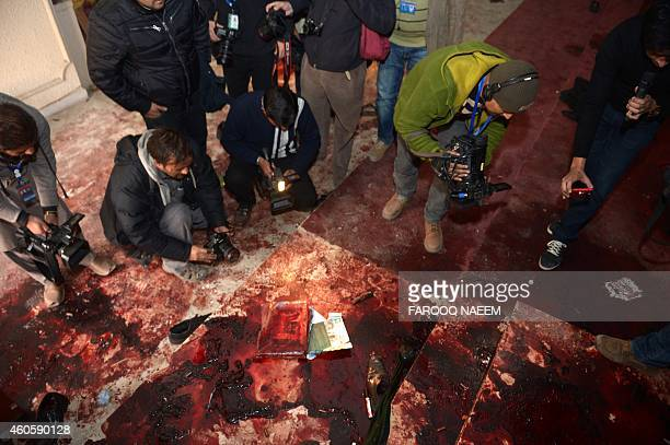 Pakistan media take footage of the bloodied floor at an armyrun school a day after an attack by Taliban militants in Peshawar on December 17 2014...