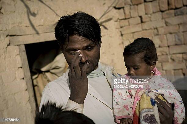 Pakistan Mohamed Ijaz , wipes a tear outside his five meter square room as he holds his 6 month-old daughter Bilal after a day's work at a brick...
