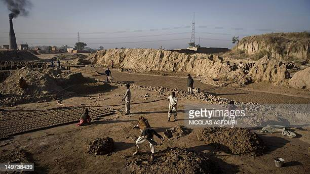 Pakistan Mohamed Ijaz , works at sunrise with his brother Mohamed Riiz , father Karm Ali , and other members of the family at a brick factory in...