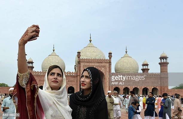 Pakistan muslim women take selfie photographs after offering Eid al-Fitr prayers at the Badshahi Masjid in Lahore on July 6, 2016. The three-day...