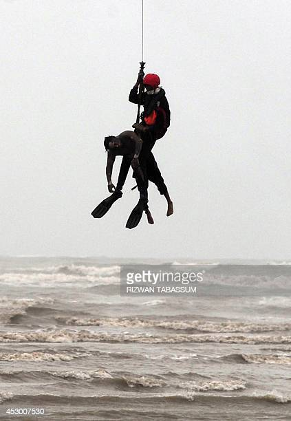 Pakistan Navy rescuer, hanging from the winch line of an unseen Sea King helicopter, recovers the body of a drowning victim at Clifton beach in...