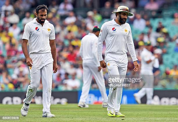 Pakistan paceman Wahab Riaz and captain MisbahulHaq walk back to their mark as Australia's batsmen punish the bowling during the first day of the...