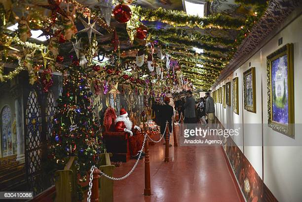 Pakistan people look a man dressed as Santa Claus during the inauguration of Pakistan's first special Christmas train at Margalla Railways Station in...