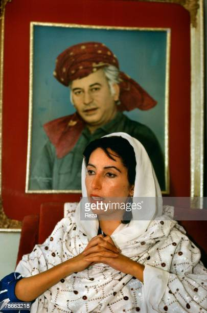 Pakistan People's Party candidate Benazir Bhutto sits in front of a portrait of her father Zulfikar Ali Bhutto inside her family home after returning...