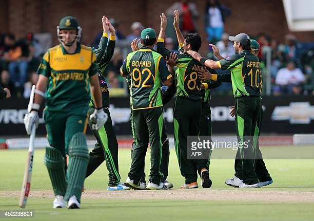 Pakistan players celebrate as South Africa's Graeme Smith walks off after losing his wicket on November 27 2013 during the second One Day...