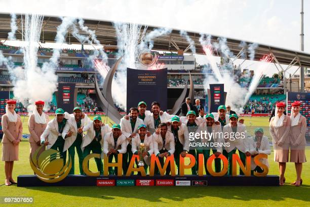 TOPSHOT Pakistan players pose with the trophy as they celebrate their win at the presentation after the ICC Champions Trophy final cricket match...