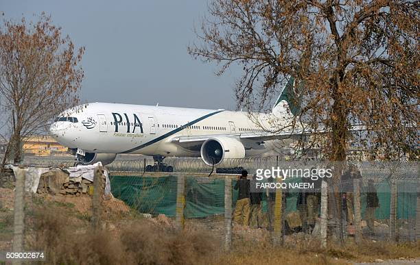 Pakistan policemen stand guard as a Pakistan International Airline plane taxis on the runway on the way to Saudi Arabia during the PIA employees...