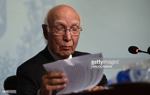 Pakistan Prime Minister Adviser on National Security and Foreign Affairs Sartaj Aziz looks at a copy of his statement at a press briefing in...