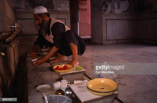 Pakistan Punjab Lahore Badshahi Mosque Interior with Muslim pilgrim preparing meal